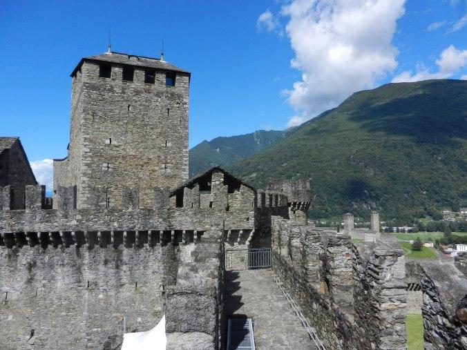 Die zinnenbewehrten Mauern des Castello di Montebello. Rechts sind die Türme des Castelgrande zu sehen.