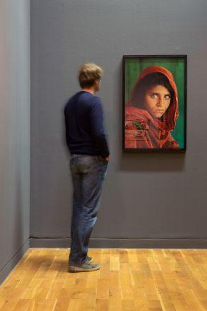 """Installationsansicht """"Steve McCurry – Im Fluss der Zeit. Fotografien aus Asien 1980-2011  Kunstmuseum Wolfsburg 19.01. – 16.06.2013 Afghanisches Mädchen – Sharbat Gula. Peshawar, Pakistan. 1984. © Steve McCurry / Magnum Photos"""