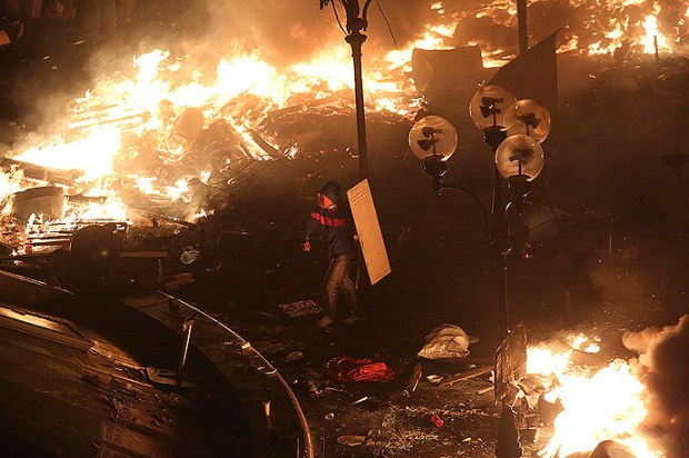 An anti-government protester holds a shield as he walks amidst flames during clashes with Interior Ministry members and riot police in central Kiev