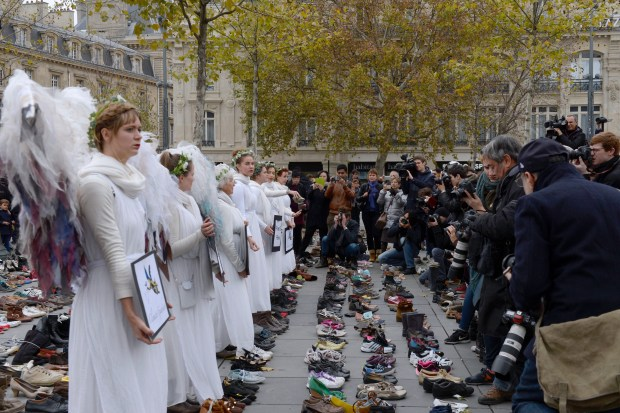 "Women dressed as angels holds signs at the Place de la Repubique where hundreds of pairs of shoes were places earlier, on November 19, 2015, on the eve of the official opening of the COP21 UN Conference on climate in the French capital Paris. The shoes were placed as part a symbolic and peaceful rally called by the NGO Avaaz or Voice ""Paris sets off for climate"". AFP PHOTO / MIGUEL MEDINA / AFP / MIGUEL MEDINA (Photo credit should read MIGUEL MEDINA/AFP/Getty Images)"