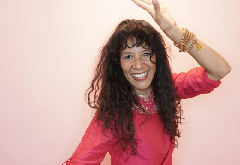 Charisma Whitefeather, Kundalini Yoga teacher in Los Angeles, wearing a bright pink kurti, dancing and smiling