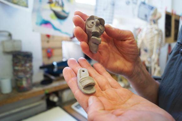 Zwei Hände, die zwei kleine Tonobjekte halten: einen Schuh und ein Gesicht