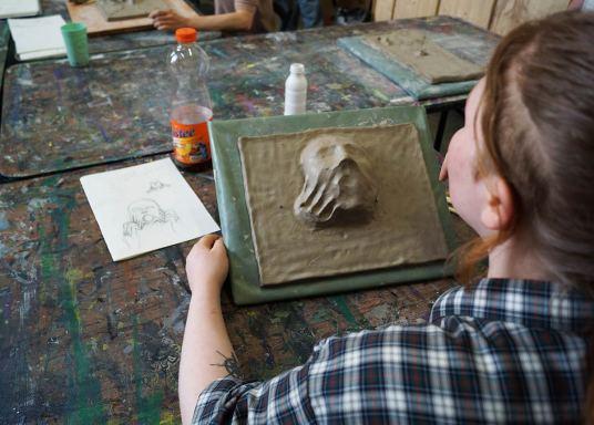 Teilnehmerin, die das Relief/Gesicht anfertigt