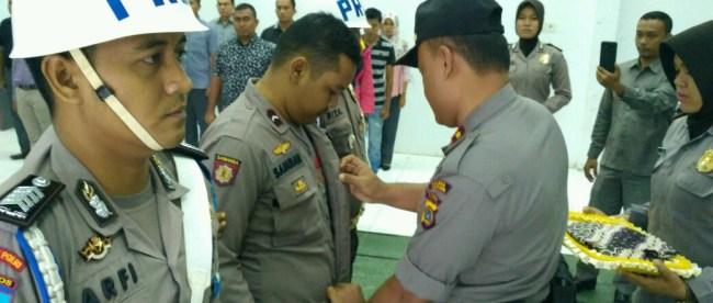 Wakapolres Aceh Utara Kompol Suwito memakaikan baju batik kepada personel yang diberhentikan tidak hormat (photo/rils/Ist)