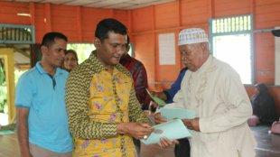 Kepala BPN Langsa menyerahkan sertifikat tanah kepada warga Gampong Buket Metuah, Sabtu 17/3 (dok. KM)