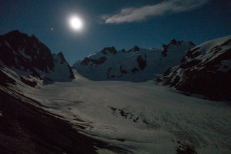 View of the summit, snow dome on the right and blue glacier below. Lit by moonlight.