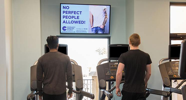 Two men on treadmills with a digital signage tv above them promoting services
