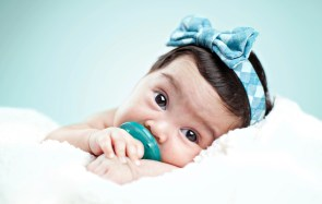 Gorgeous baby girl laying on a blanket with pacifier in her mouth