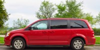 Red colored Dodge Grand Caravan parked on the street.