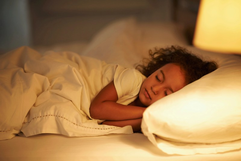 A cute little girl fast asleep in a double bed