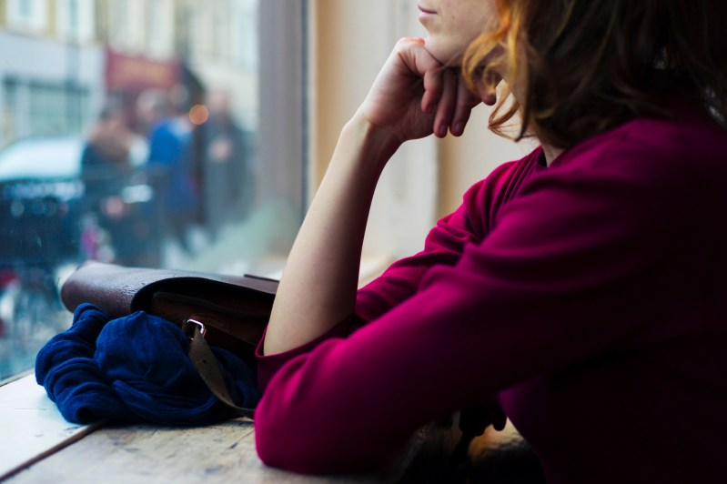 A young woman is sitting by a window and is looking out and day dreaming