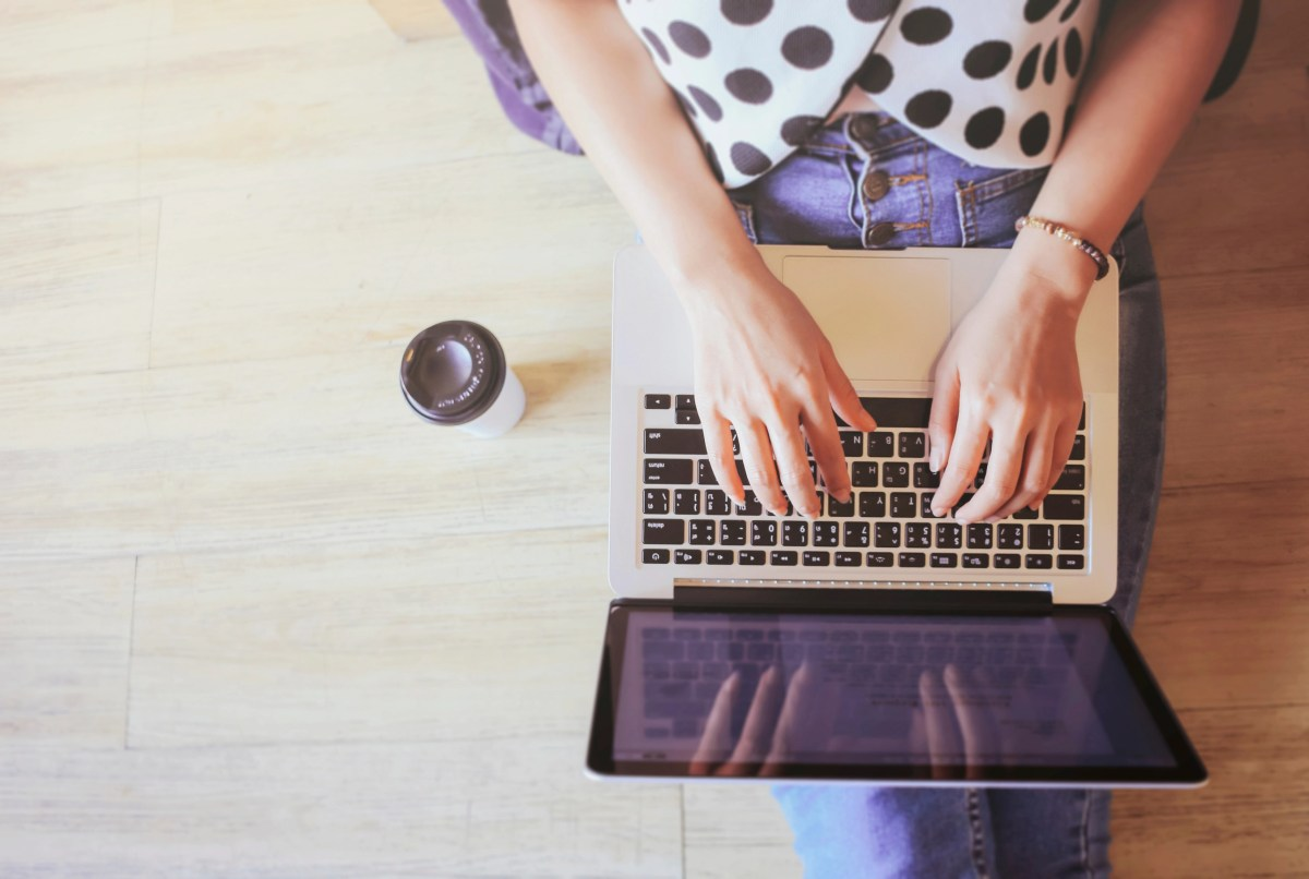 Top view of laptop in girl's hands sitting on wooden floor with coffee