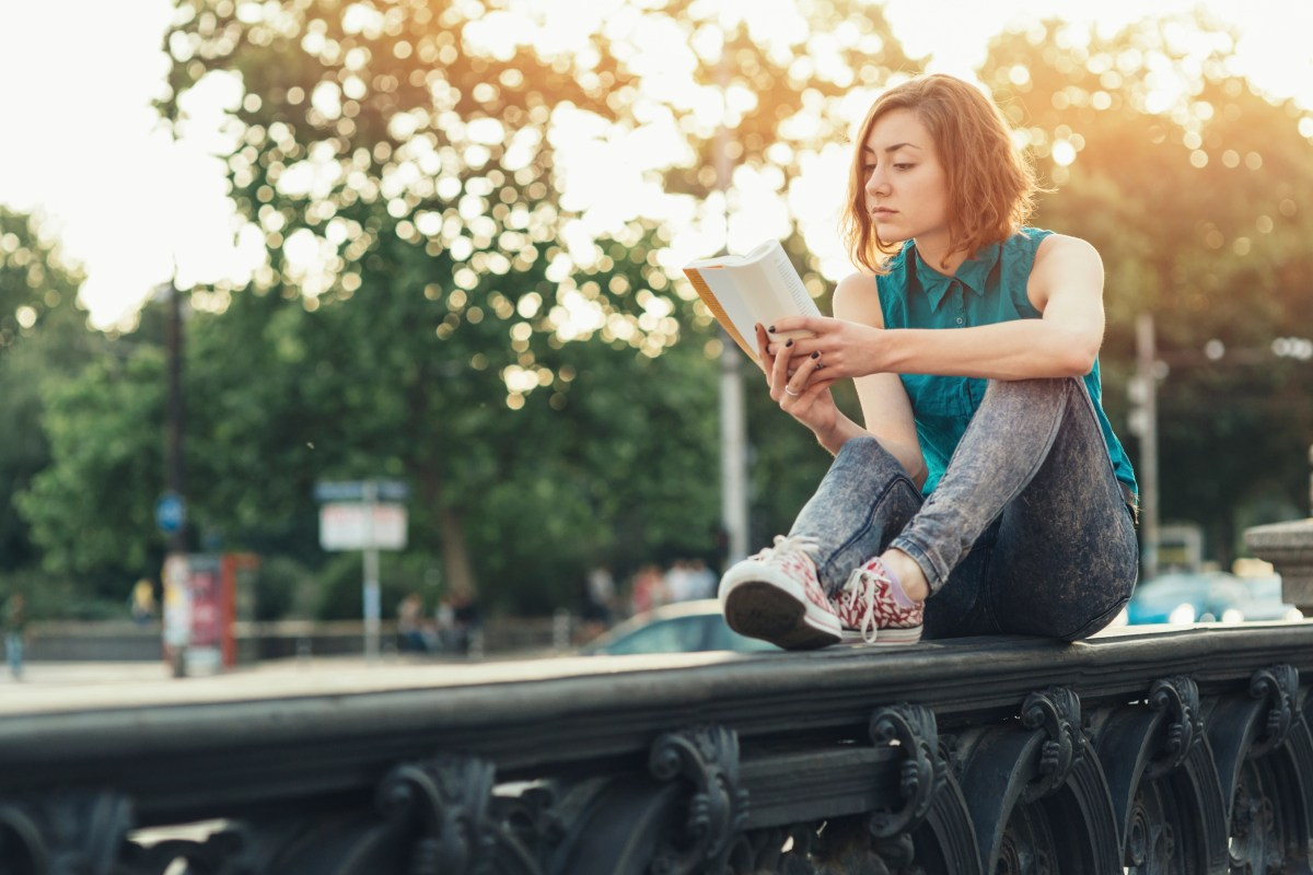 Teenage girl reading a book while sitting on a bridge near big boulevard.