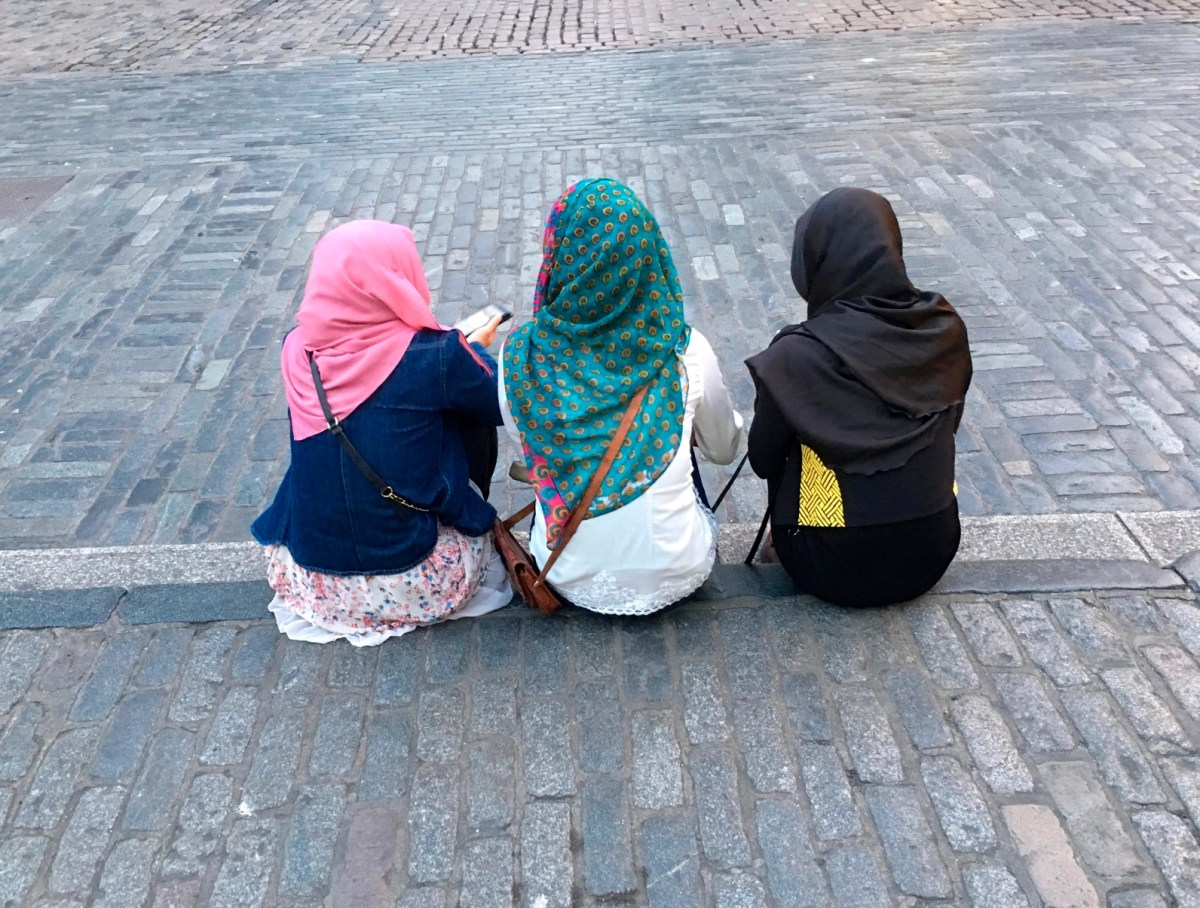 London, England - May 28, 2016: Three young muslim girls, with ritual headscarves, sit and text from smart-phones from a curb at Covent Garden.