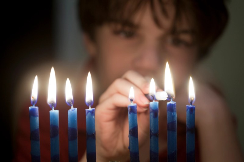 boy lighting menorah