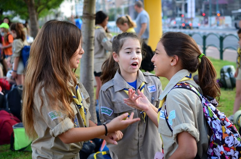 Kfar Saba, Israel - July 19, 2013: Three Israel Scouts girls in a lively discussion getting ready to leave for summer camp on early Friday morning