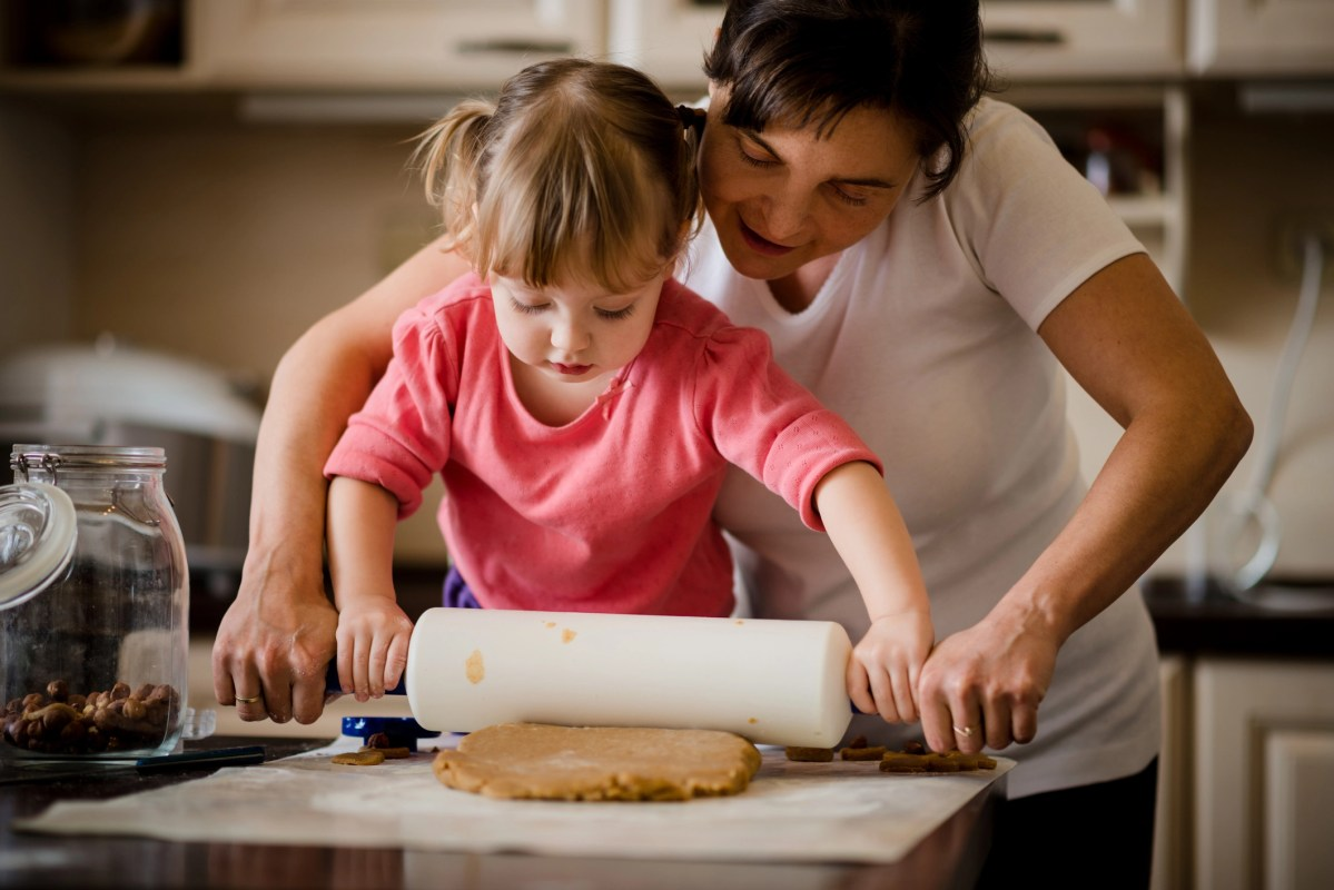 Mother and child preparing dough with rolling pin in kitchen at home