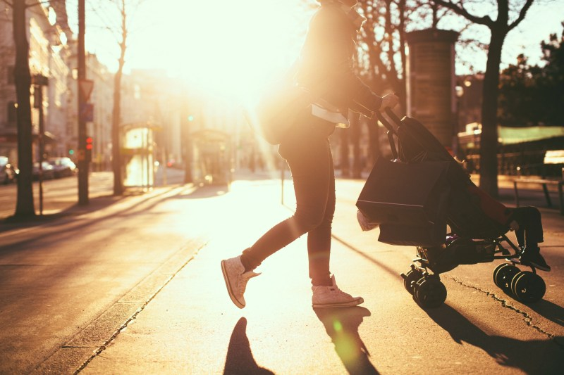 Photo of a modern mom having an easy walk and shopping with her baby in the strollers, outdoors in the city