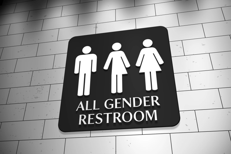 "A sign on a wall for ""All Gender Restroom"" with symbols for men, trans and women. LGBT issue."