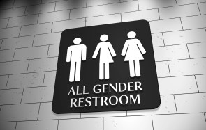 """A sign on a wall for """"All Gender Restroom"""" with symbols for men, trans and women. LGBT issue."""