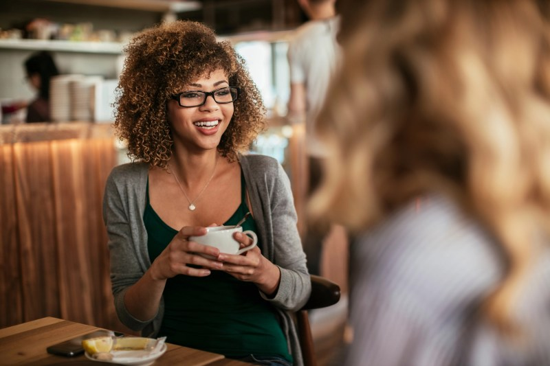 Close up of a young women drinking coffee and having a conversation .