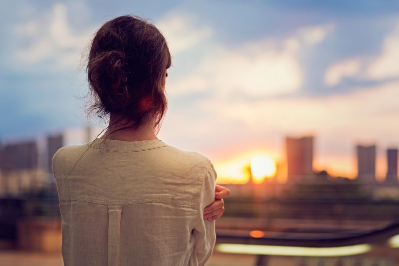 Young girl is watching sunset over Tokyo in Odaiba.