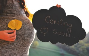 "Pregnant woman in the autumn park , holding a sign that says ""Coming soon""."