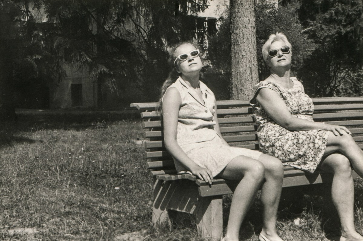 Vintage photo of mother and daughter in sunglasses sunbathing on bench, sixties, Poland