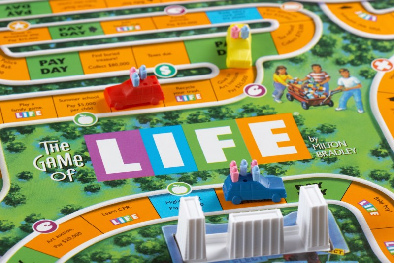 Oxford, Connecticut, United States - September 6, 2011: Playing, The Game of Life. Life is a board game originally created in 1860 by Milton Bradley. Later reproduced by the Milton Bradley Company in 1960. Life was America's first popular parlor game and is still very popular today. In this board game the player's travel around the board in a car. Along the way they will find themselves leaving college and choosing a carrer as well as getting married and possibly having children. The game ends when the players make it to retirement. There are many ups and downs during the game such as having to pay taxes, winning the lottery, having your salary change, simulating real Life.