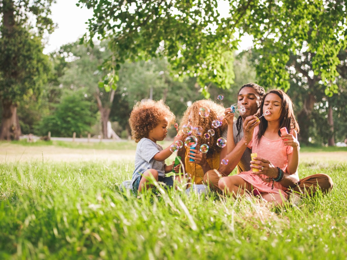 Cute african-american family sitting in a gorgeous picturesque park while playing with their kids and blowing bubbles on a beautifull sunny afternoon