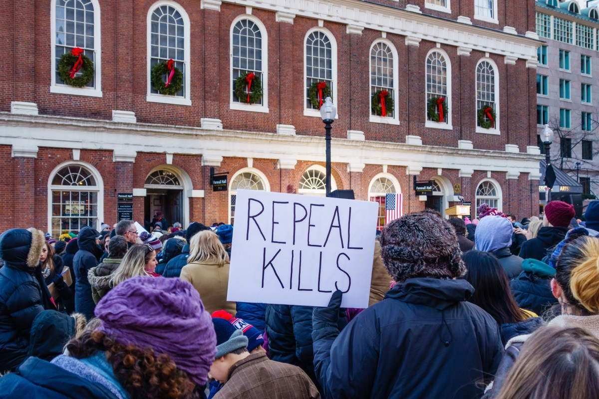 """Boston, MA, USA-January 15, 2017. Protester with sign on her back at"""" Our First Stand: Save Healthcare Rally"""" where Elizabeth Warren spoke to audience in front of Fanueil Hall."""