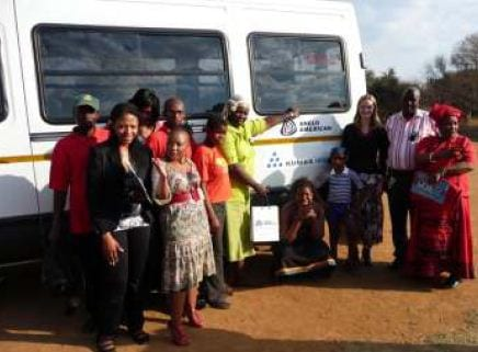 Right to left: Ms Beauty Maguga, Mr Radikwega Selomo (Community Leader Smash Block), Ms Sarah Morrison, Ward Councilor Annah Makola, Ms Priscilla Pholoto (Head of Sustainable Development, Kumba), Ms Lerato Thobejani (Communications Officer, Kumba) with Home Base Carers (in red shirts) and kids