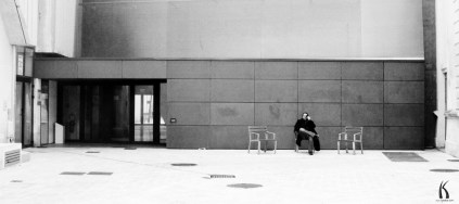 Outdoor portrait of the image creative and photographer Kyesos sitting on a bench