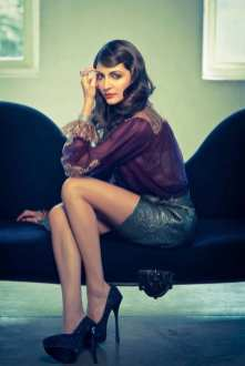 Anushka Sharma dans un look total vintage: jupe en cuir d'un vert sombre et une chemise transparente violette.