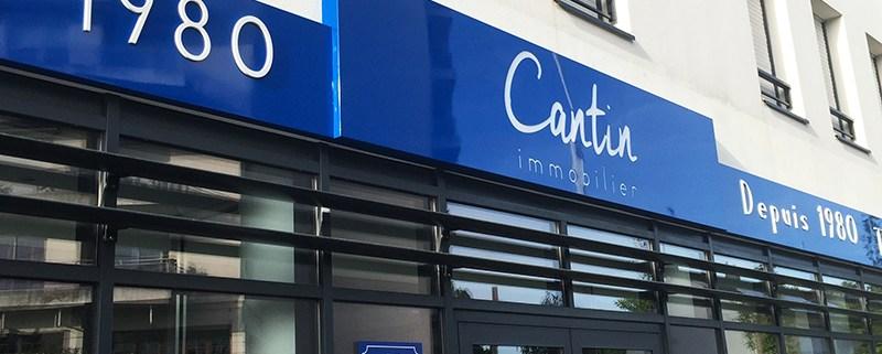 Enseigne caisson lumineux - Création et pose de l'enseigne en vitrine Cantin Immobilier, avec caisson lumineux à Saint Herblain - Label Communication