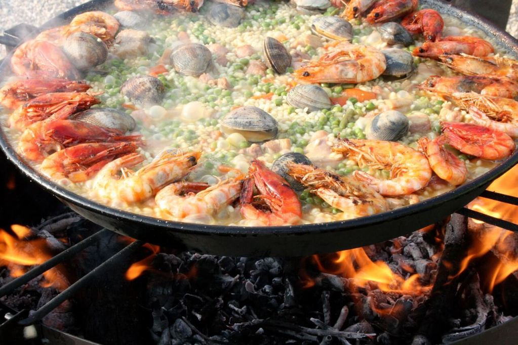 a beautiful paella, Spanish typical dish, filled with shrimps and seafood, ready to be served to eat.