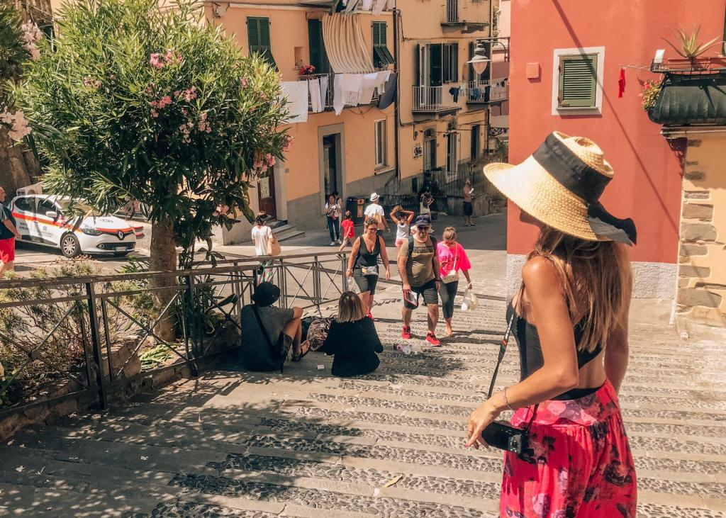 Ana Palombini exploring Riomaggiore's beautiful village, wearing a pink skirt and holding her camera for vlogging her travels. #mistake