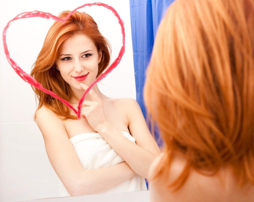 girl in love with herself in the mirror with a hart drawn on it