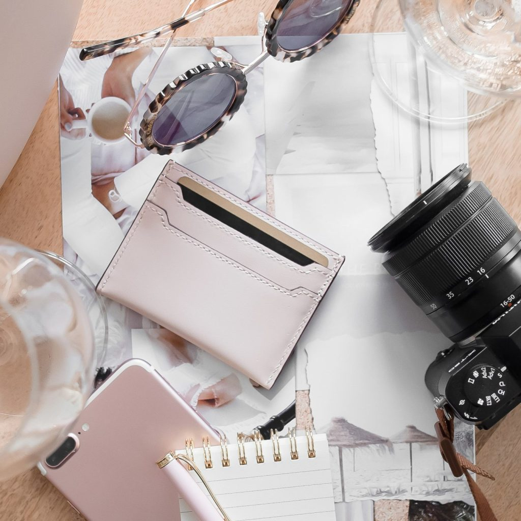 flat overlay of a camera, wallet, phone and sunglasses in pink tones
