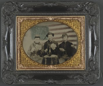 Three unidentified soldiers playing cards, smoking, and drinking in front of American flag