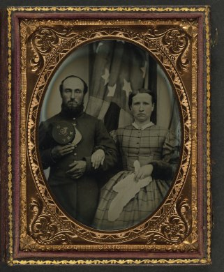 Unidentified soldier in Union frock coat holding Company G, 12th New Hampshire Infantry Regiment forage cap next to unidentified woman in front of an American flag2