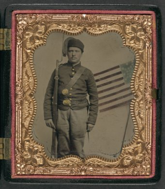 Unidentified soldier in Union uniform and fez with bayoneted musket in front of painted backdrop showing American flag2