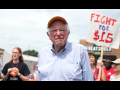 Photo of Bernie Sanders in front of Fight for $15 sign.