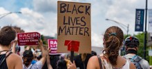 """Crowd viewed from back. Sign in foreground, hand-lettered: """"Black Lives Matter."""" Signs in background, printed: """"Racism is a public health crisis"""" with the logo of National Nurses United"""