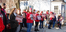 A crowd holding signs saying Support Somerville Educators and Living Wage for Paras