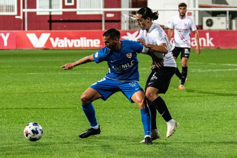 Luismi Cruz, jugador del Sevilla Atlético, en la disputa de un balón con un jugador del Linares Deportivo