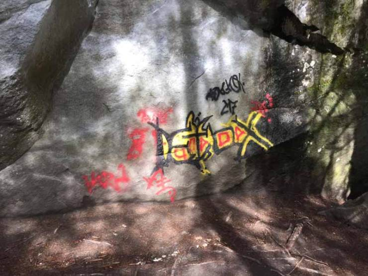 Graffiti an Boulderblock im Magic Wood - Schmiererei