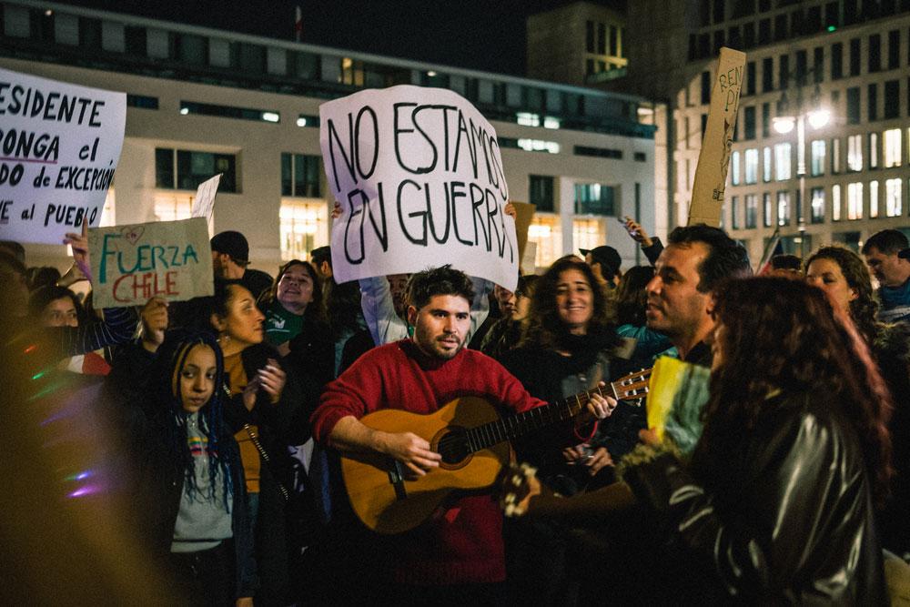 No estamos en guerra reza la pancarta de uno de los manifestantes a raíz de los dichos del presidente Piñera quien calificó la situación actual como un estado bélico - oto: Ramón Vásquez Lemus - Lado|B|erlin