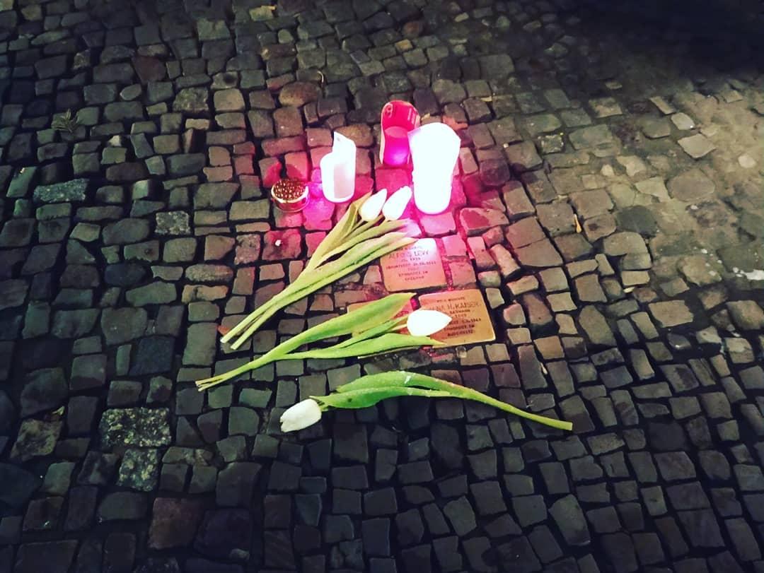 Las personas dejan velas en recuerdo de los asesinados por el nazismo en las placas del artista alemán Guter Demnig, Stolpersteine.