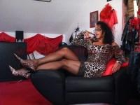 Domina Lady Alina sitzt auf einen Sessel